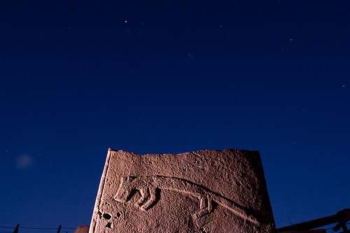 ©Nico Becker. A pillar with a low-relief carving at night